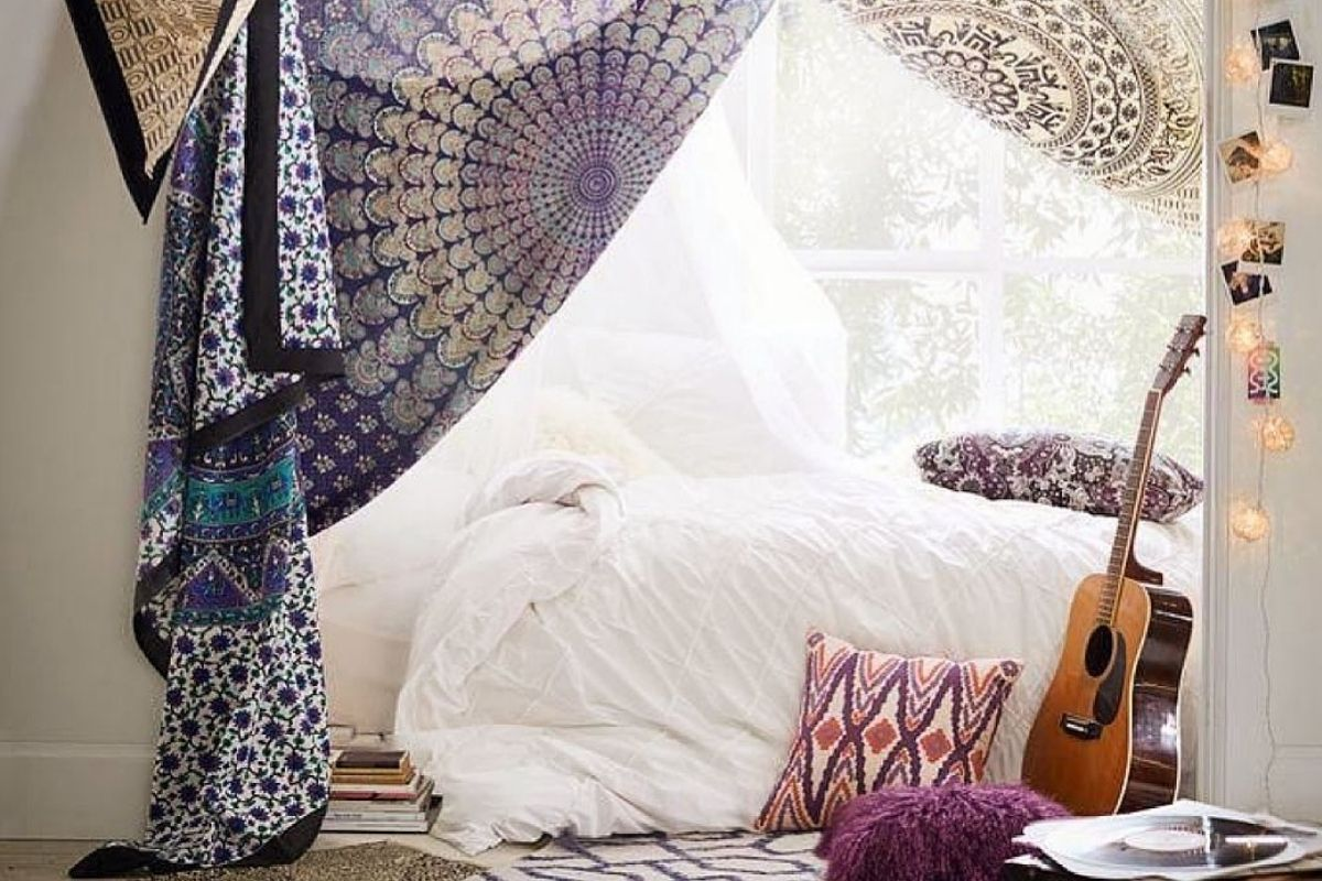 hippy curtains hanging over a bed and a guitar