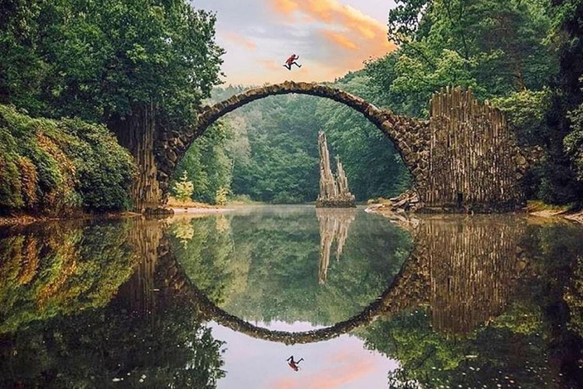 fantasy scene of person jumping over bridge with trees and river