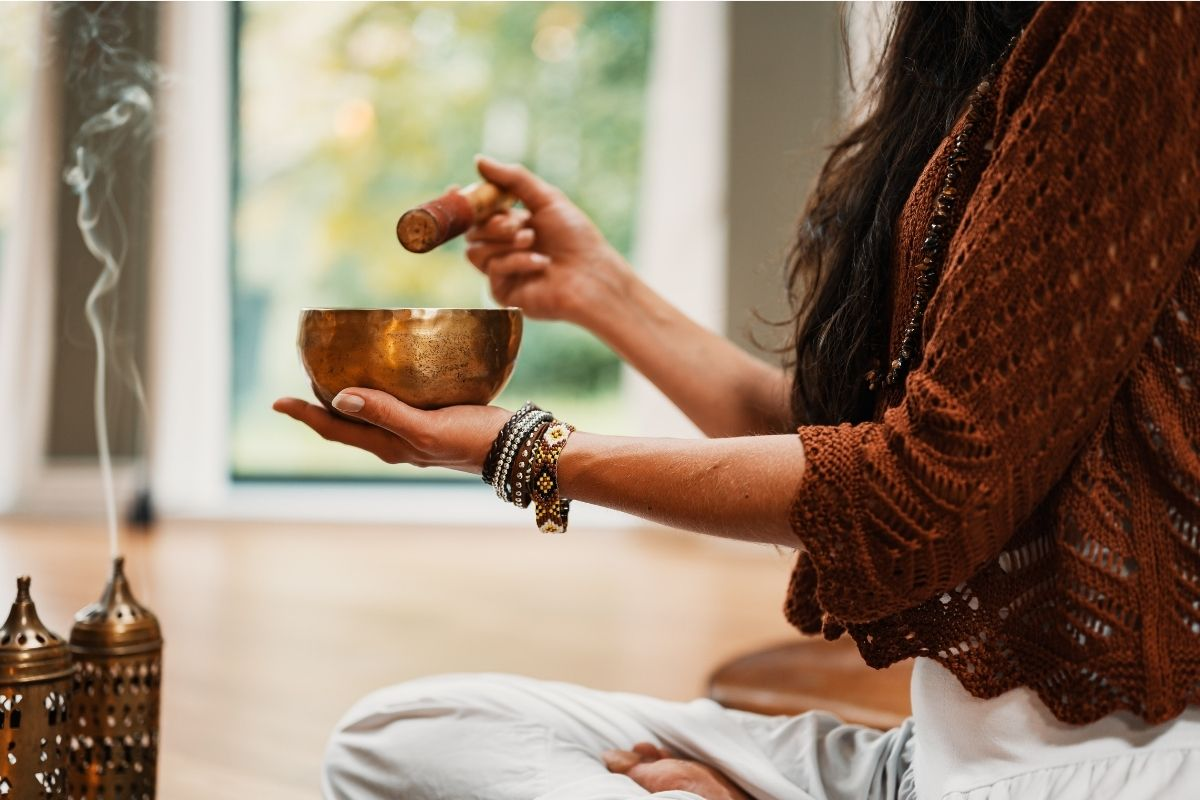 woman crosslegged with singing bowl and gemstones for meditation