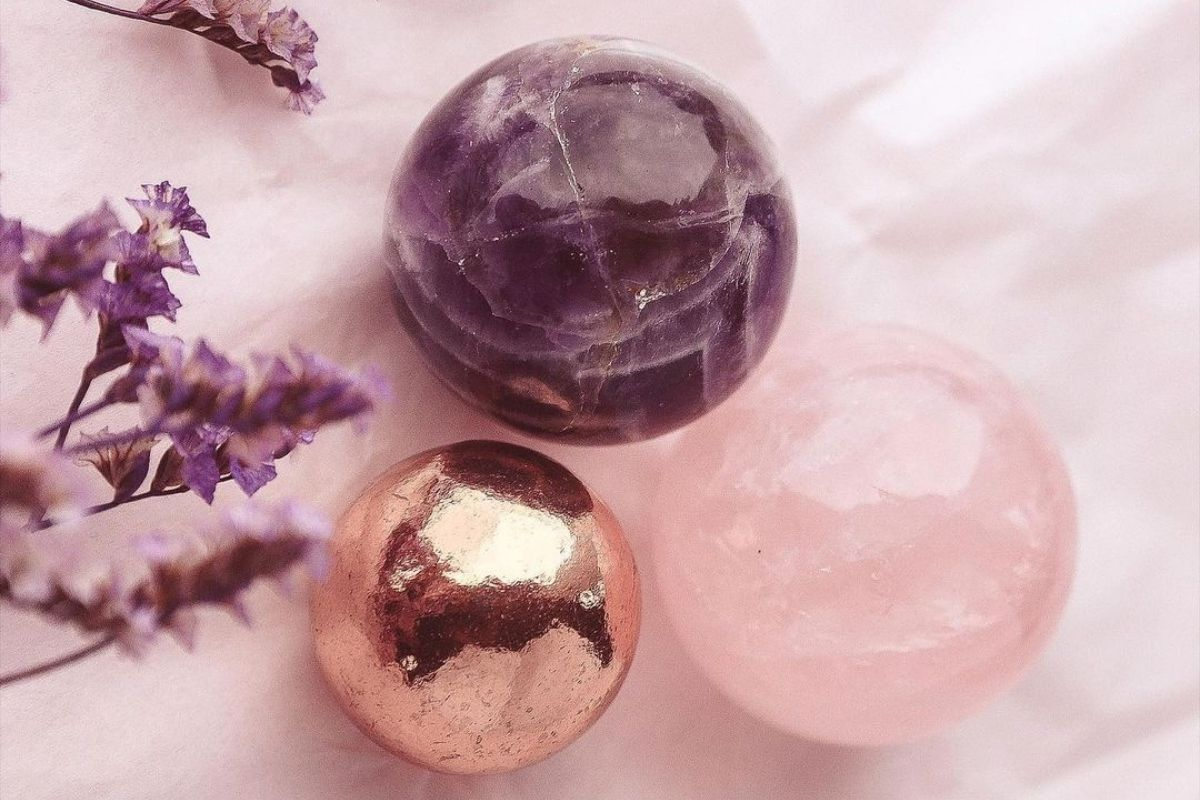amethyst sphere, rose quartz sphere, and copper ball as examples of true crystals