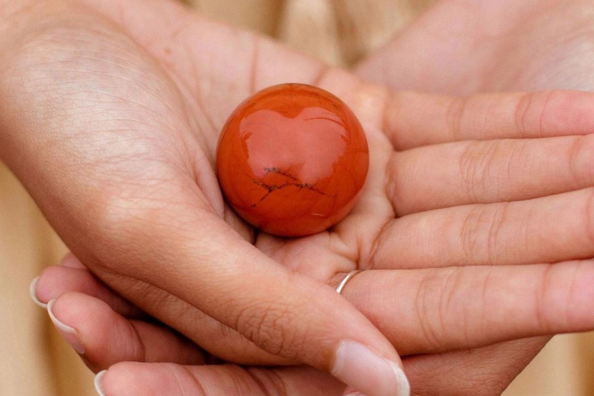 hands holding red jasper sphere