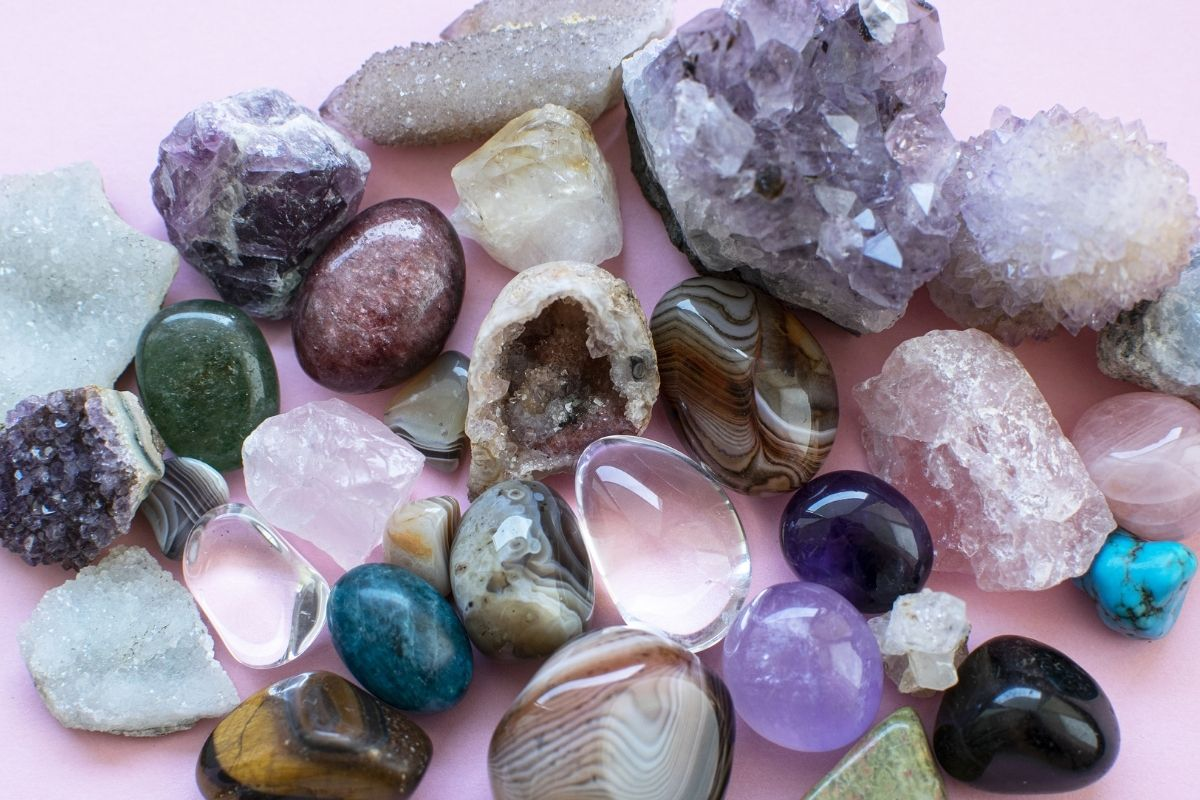 selection of crystals and minerals against pink background