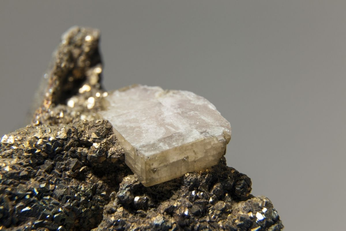 rhombic crystal of white calcite growing on chalcopyrite crystals