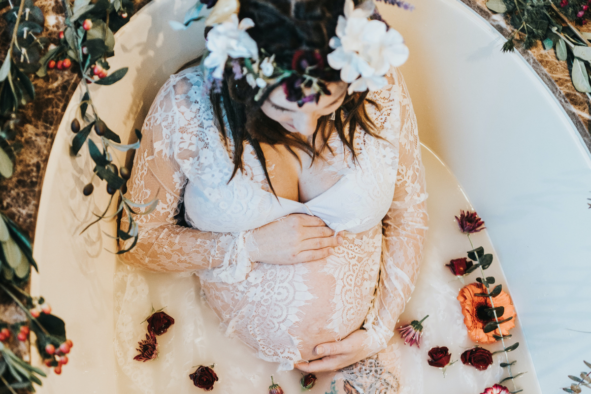 pregnant woman in bath with flowers and crystals for fertility