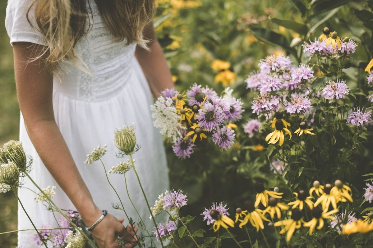 woman in white dress and field of flowers