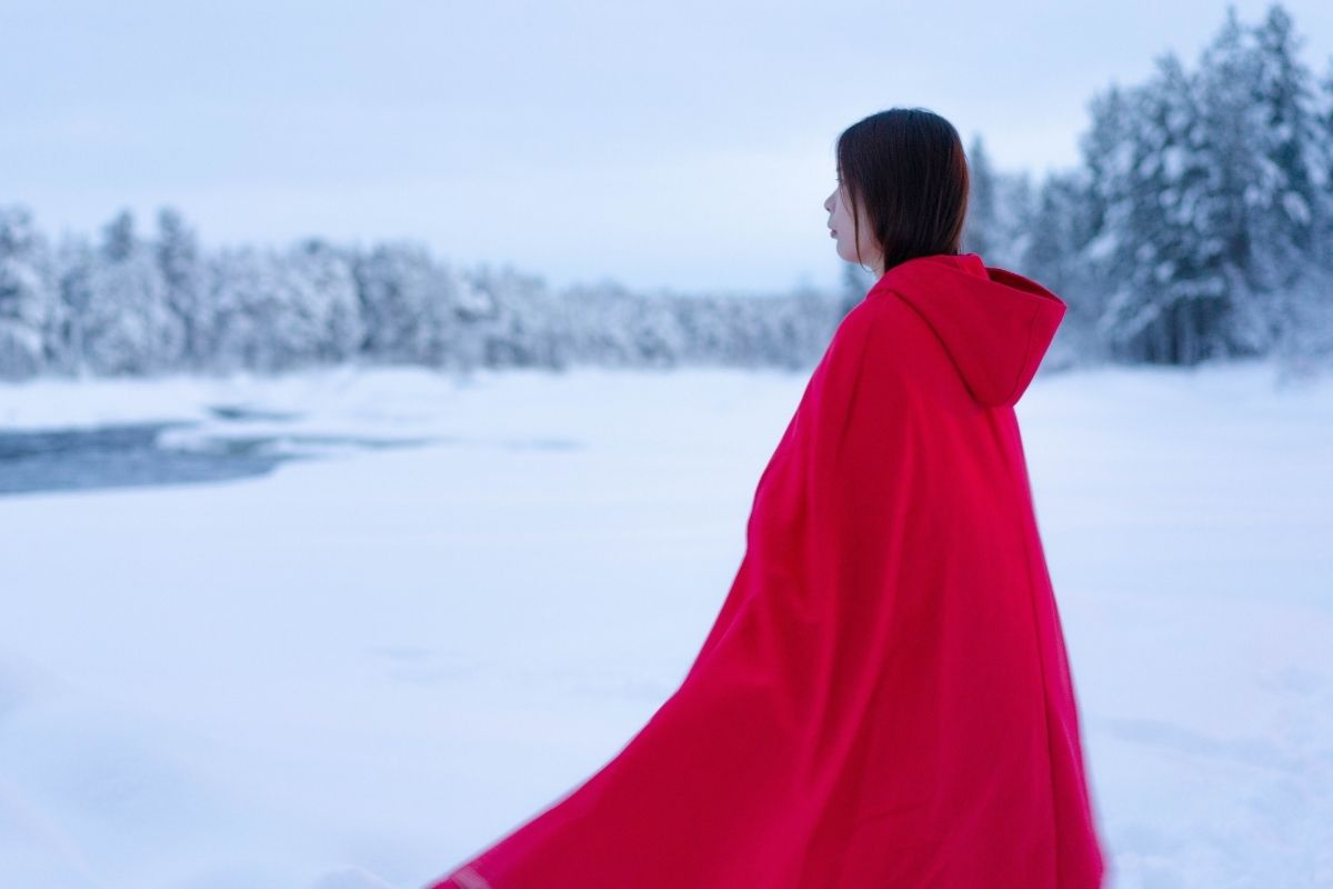 woman wearing red cape against snowy backdrop