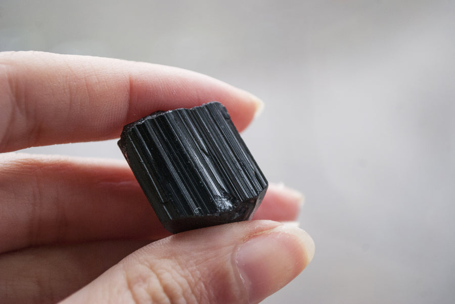 person holding black tourmaline stone