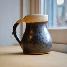 Load image into Gallery viewer, A Black and Cream Soda Fired Mug
