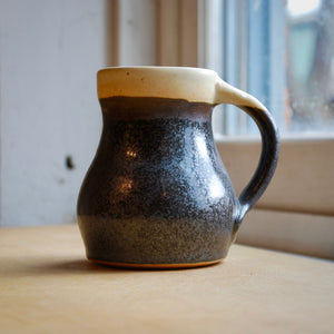 A Black and Cream Soda Fired Mug
