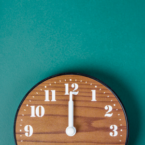 A wooden texture clock at 12.00 on a wall