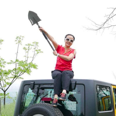 Women on top of jeep with tactical shovel