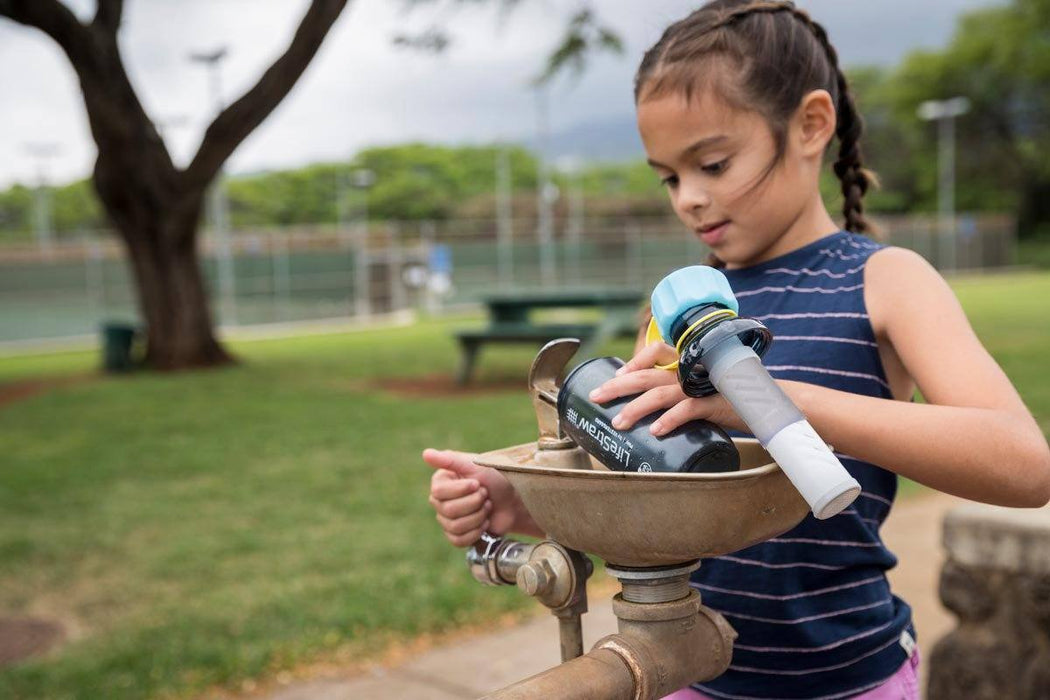 LifeStraw Play Kids Water Filter Bottle in use at a public water fountain