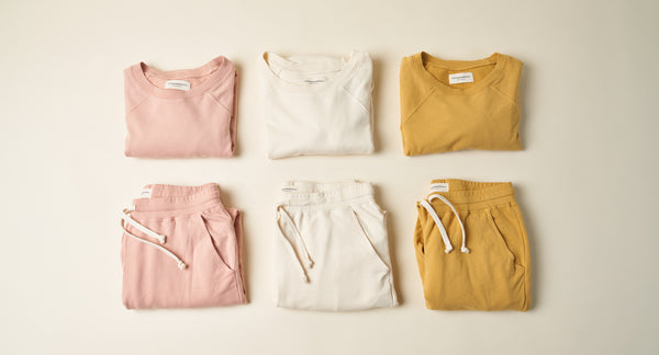 Group of folded jogger and sweatshirt sets. Colors are Pale Pink, Bone and Golden