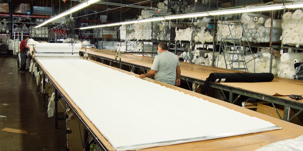 worker rolling out a large roll of white fabric onto a cutting table