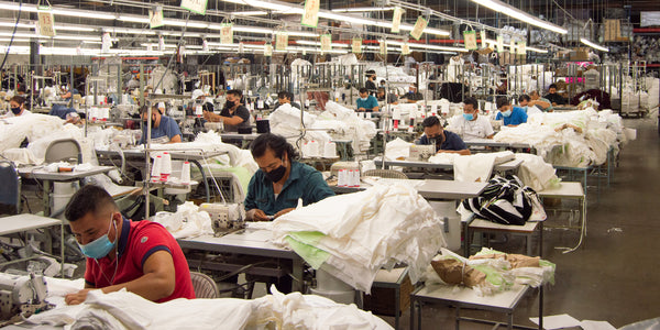 group of workers sitting behind sewing machines sewing new clothing at our LA factory