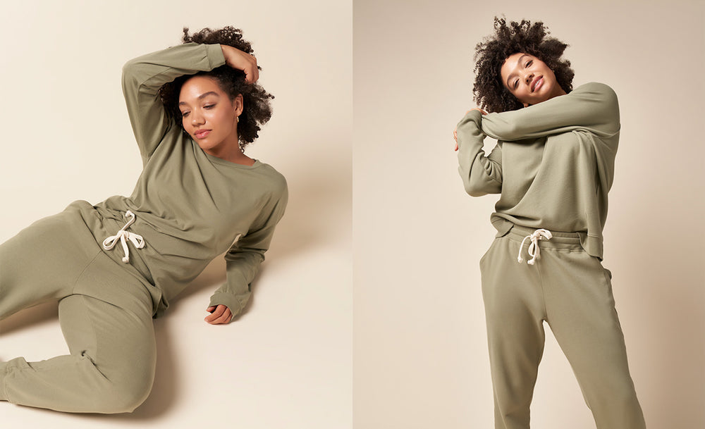 Two images of the same model. On left model laying down and the right standing up. Both images are in the recycled and organic cotton jogger and college pullover sweatshirt outfit in Sage Green