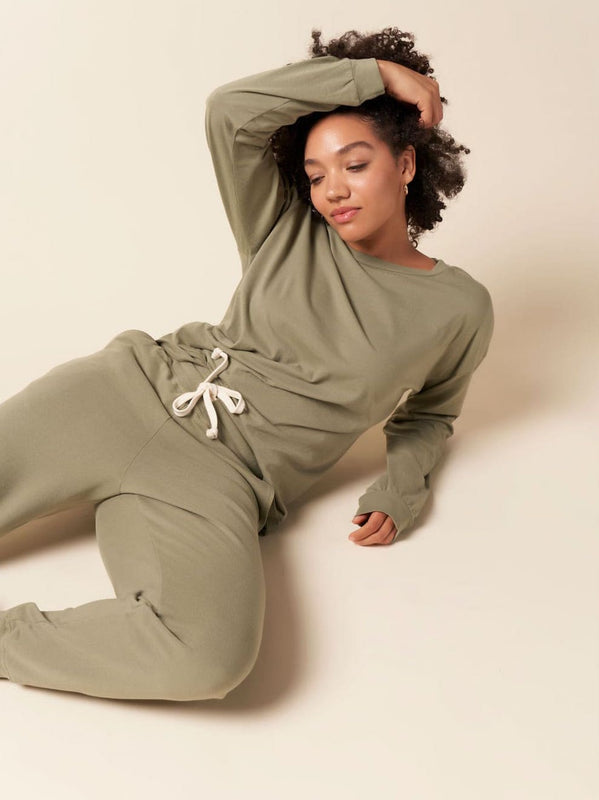 Model laying down wearing the organic and recycled cotton college pullover sweatshirt outfit in sage green.