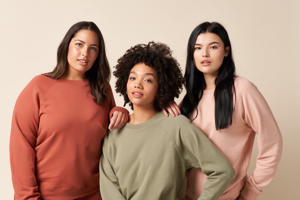 Group photo with three models. All wearing the recycled and organic cotton college pullover sweatshirt. Colors from left to right are clay, sage and pale pink