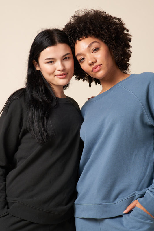 Picture of two models standing. Each wearing the recycled and organic cotton college pullover sweatshirt. Colors are vintage black and stone blue