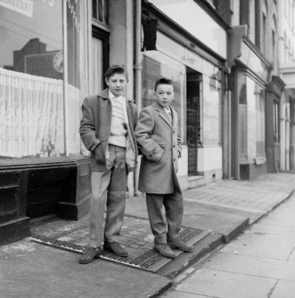 Two young 'teddy boys' pose in the street: 1960