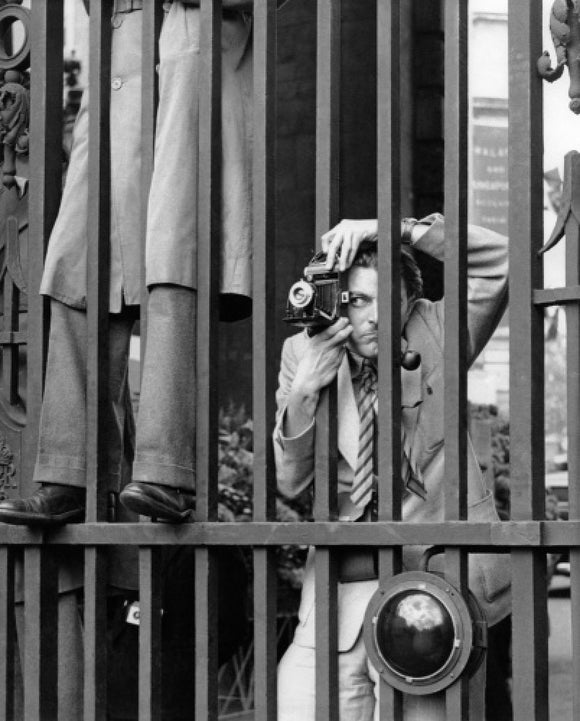 A photographer takes a picture through the railings at Admiralty Arch: 1953