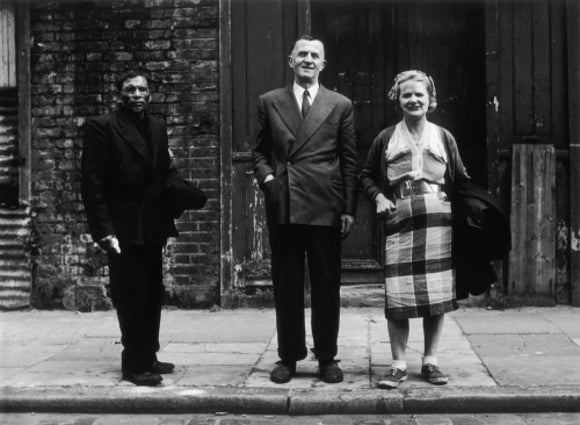 Three people stand on street facing the camera: 1961