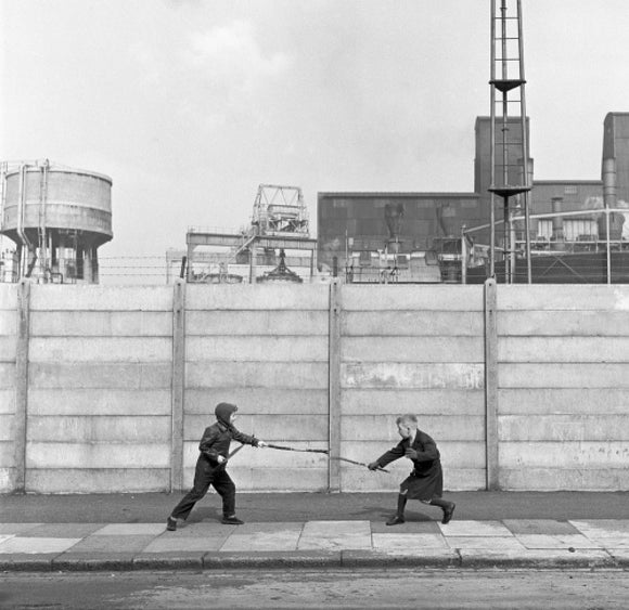 Two boys fighting with sticks in front of a concrete wall. c.1955