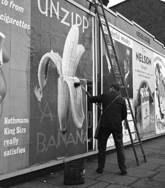 Man pastes up a billboard advertisement. c.1955