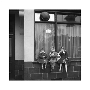 Three children perched on the windowsill of a pub. c.1955