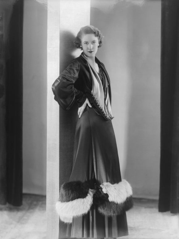 Image of a woman modeling a an evening coat; 1932