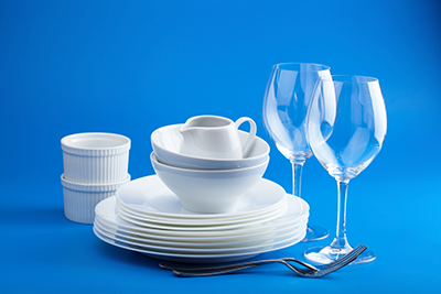 Clean and Sanitized Dishware - Plates and Glasses with a Blue Background