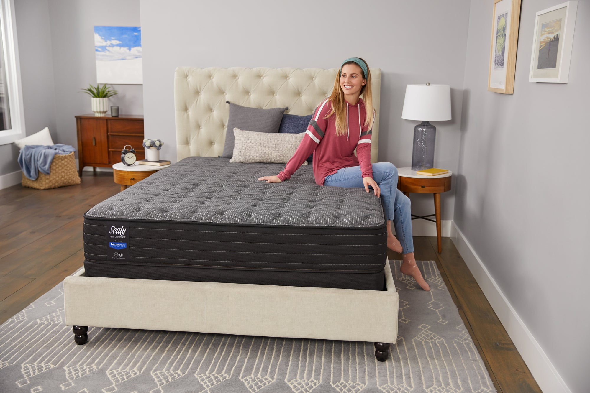 Smiling woman sitting on Sealy mattress