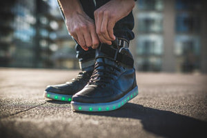 Man doing up his LED high top running shoes