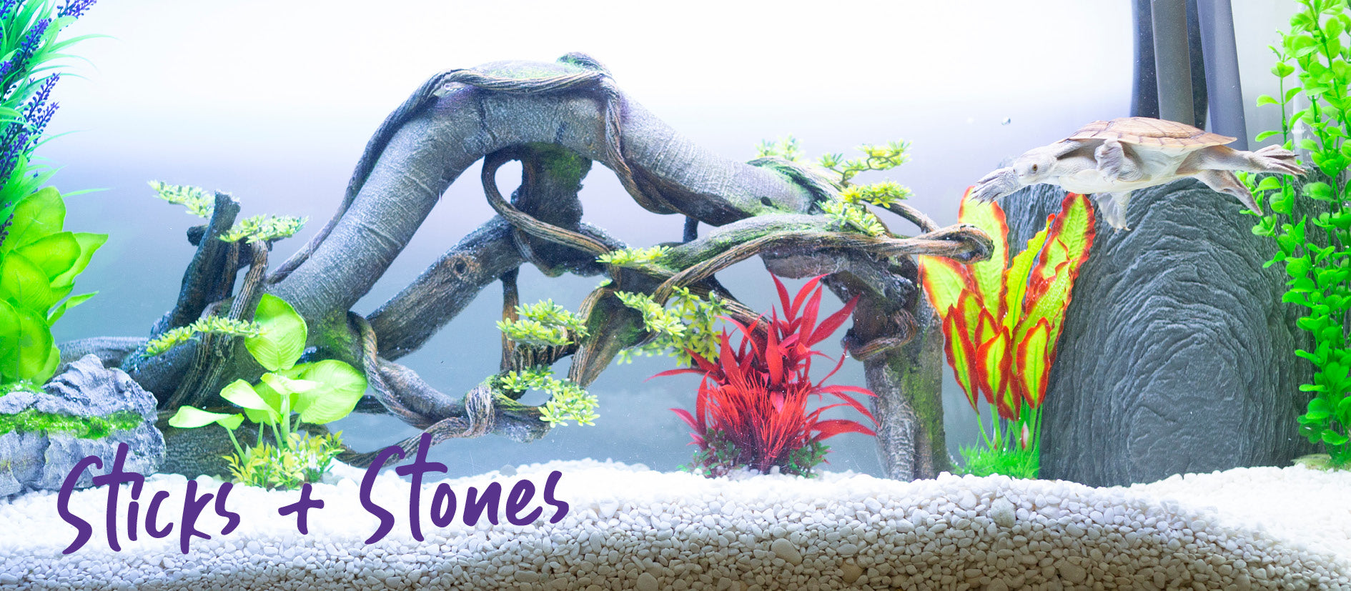 fish tank decoration with logs and stones and bright silk plants