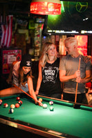 Pool table, a woman is shooting pool while another woman and a man are standing next to her.  All are wearing Barney's Beanery shirts.