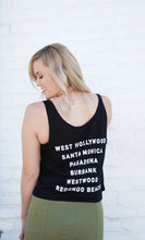 Load image into Gallery viewer, Woman standing against white wall, wearing black Barneys Beanery tank top with back facing camera; a list of Barney's Beanery locations is listed on the back.
