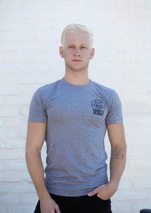 Man Wearing Grey T shirt, black logo in upper chest
