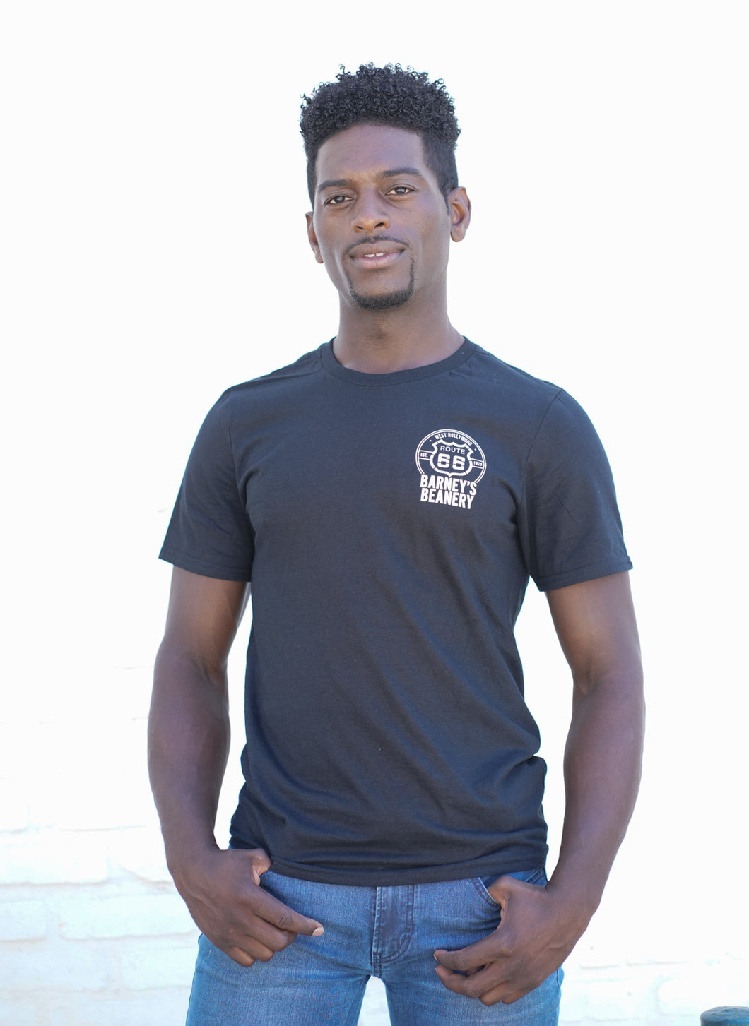 Man wearing black Barney's Beanery shirt, from the front, against a white wall