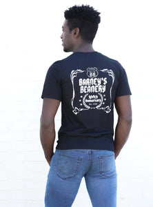 Man wearing black Barney's Beanery shirt, from the back, against a white wall