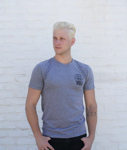 Man wearing grey Barney's Beanery shirt, from the front, against a white wall
