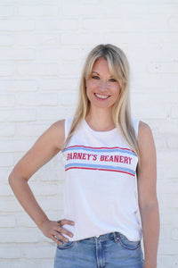 "Woman standing against white wall, wearing white Barney's Beanery Muscle T shirt; shirt has ""Barney's Beanery"" written across the front in Red and Blue lettering"