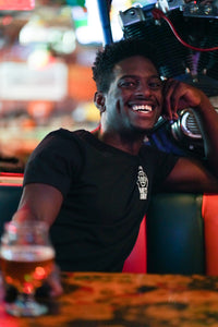 Man sitting in booth in restaurant, holding beer, smiling, wearing a black Barney's Beanery T shirt