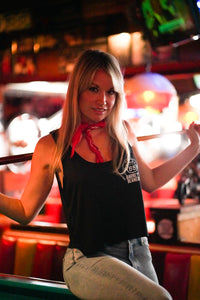 Woman sitting on pool table, facing camera, wearing black Barney's Beanery tank top with logo on left chest, and holding a pool stick across both shoulders.