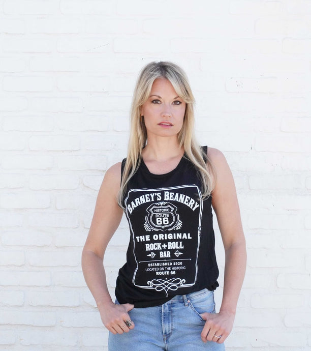 Woman standing against white wall, wearing white Barney's Beanery Muscle T shirt; shirt has Barneys Beanery Rock n Roll logo printed across the front in White lettering