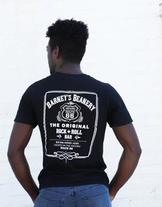 Man wearing Black Barney's Beanery Rock n Roll logo shirt, from the back, against a white wall