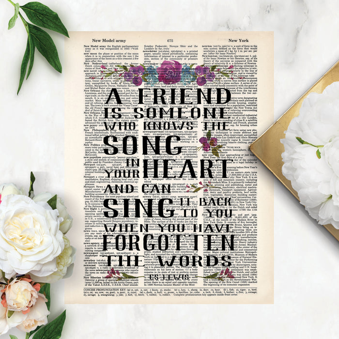 a friend is someone who knows the song in your heart and can sing it back to you when you have forgotten the words, this quote is printed on a salvaged dictionary page and has watercolor flowers in purples and blues
