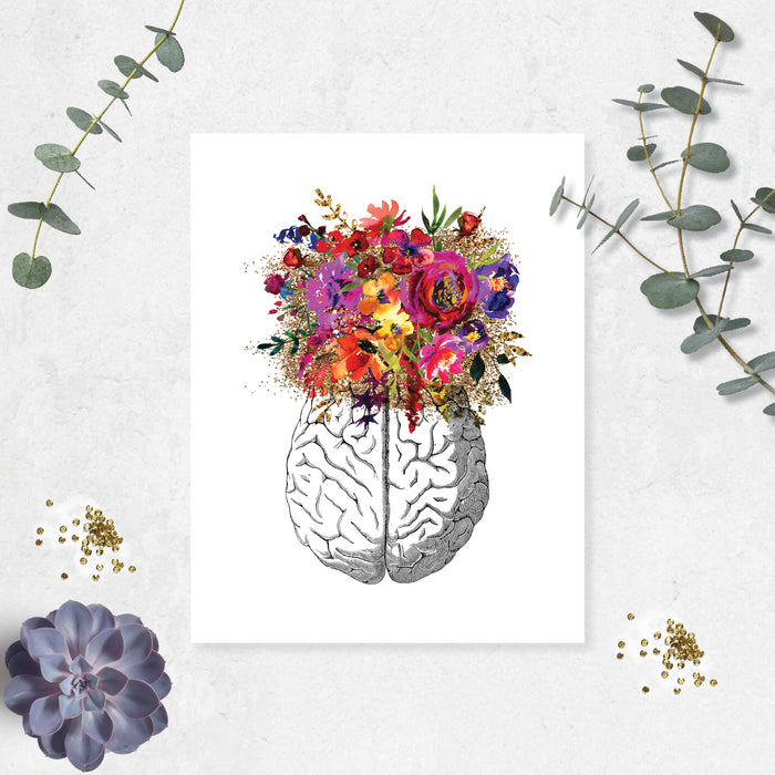 vintage etching of the top view of a brain topped with watercolor flowers in shades of pink, purple, golden and yellow toneson matte white paper