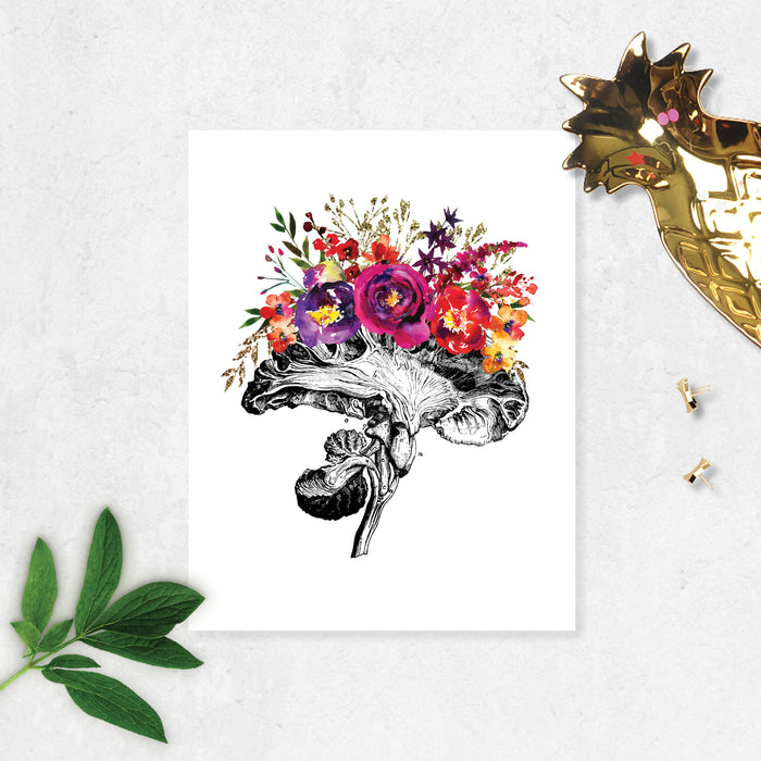 vintage etching of the cross section of an anatomical brain accented with watercolor flowers in shades of pinks, purples, and golden tones on matte white paper