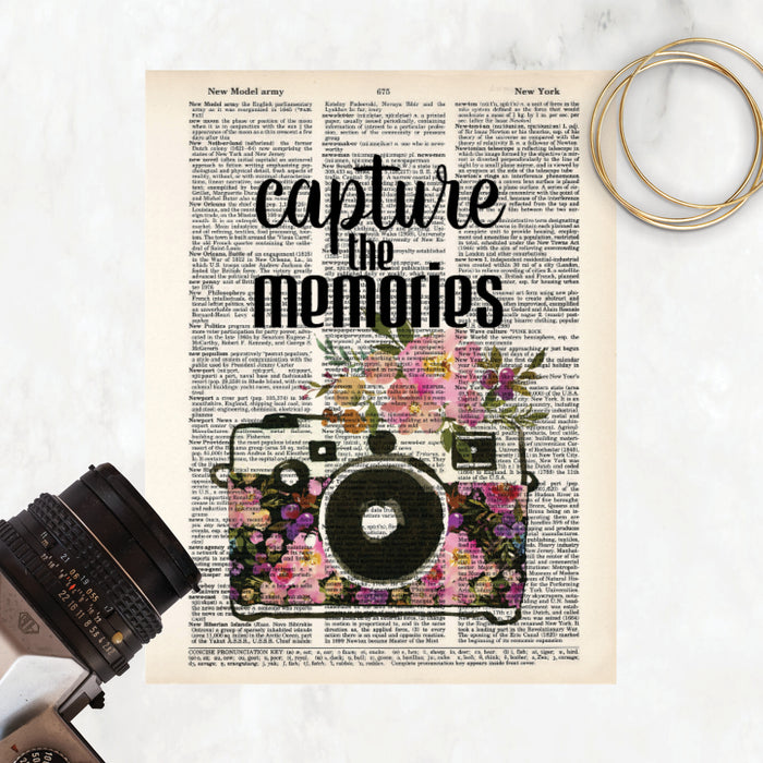 capture the memories quote and a watercolor camera decorated with watercolor flowers in pinks and purple tones on salvaged dictionary page
