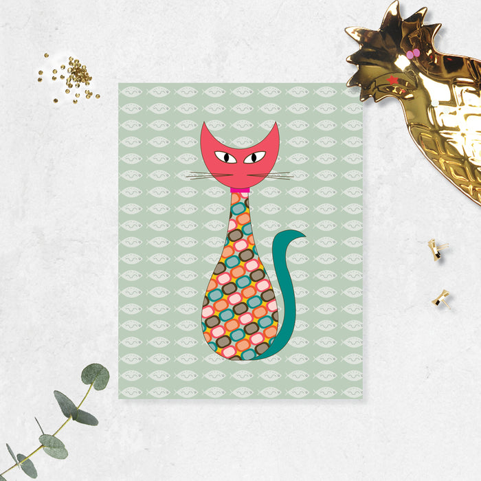 mid century modern cat styled with pink head, green tail and geometric shapes in the body, soft sage green background has shite fishes printed on matte paper